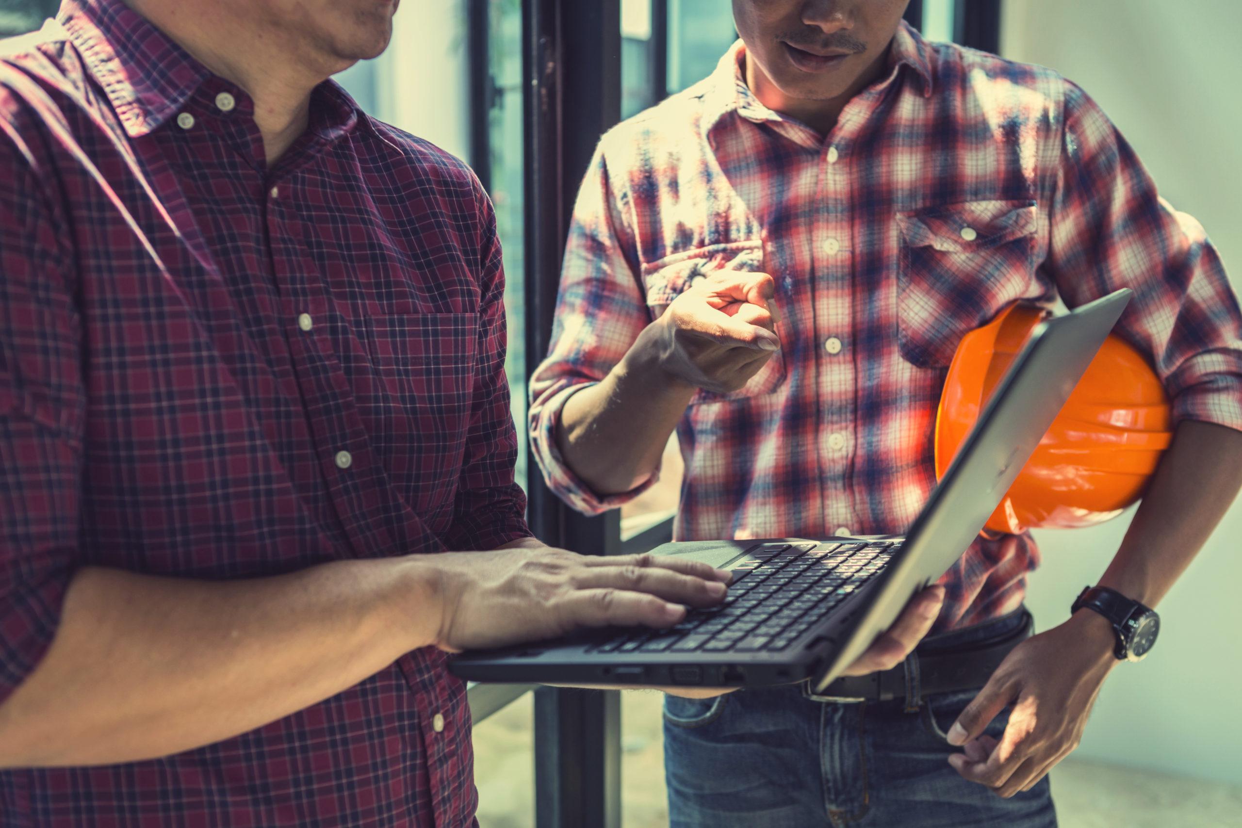 Dwóch inspektorów BHP sprawdza informacje na laptopie